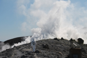 Figure at the front approaches the fumaroles with a MultiGAS unit.